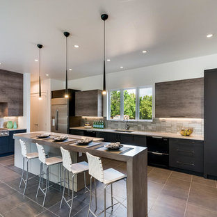 Photo of a large contemporary u-shaped open plan kitchen in Denver with an undermount sink, flat-panel cabinets, quartz benchtops, metal splashback, stainless steel appliances, porcelain floors, grey floor, black cabinets, metallic splashback and multiple islands.