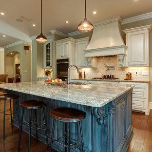 Exempel på ett stort klassiskt kök, med en undermonterad diskho, luckor med upphöjd panel, vita skåp, granitbänkskiva, beige stänkskydd, stänkskydd i terrakottakakel, rostfria vitvaror, mellanmörkt trägolv, en köksö och brunt golv