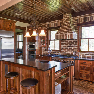 Mid-sized traditional eat-in kitchen pictures - Example of a mid-sized classic l-shaped brick floor and red floor eat-in kitchen design in Charleston with an undermount sink, flat-panel cabinets, medium tone wood cabinets, solid surface countertops, red backsplash, brick backsplash, stainless steel appliances and an island