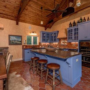 Cette photo montre une cuisine ouverte sud-ouest américain en U de taille moyenne avec un évier encastré, un placard à porte plane, des portes de placard bleues, un plan de travail en carrelage, une crédence marron, une crédence en carreau de terre cuite, un électroménager en acier inoxydable, un sol en carreau de terre cuite, un îlot central et un sol marron.