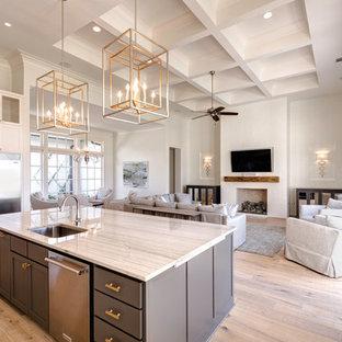 Bild på ett stort vintage linjärt kök och matrum, med en nedsänkt diskho, skåp i shakerstil, grå skåp, bänkskiva i kvartsit, vitt stänkskydd, stänkskydd i tunnelbanekakel, rostfria vitvaror, ljust trägolv och en köksö