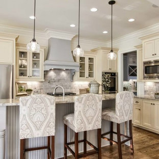 Design ideas for a mid-sized traditional galley eat-in kitchen in Nashville with a drop-in sink, raised-panel cabinets, white cabinets, granite benchtops, white splashback, terra-cotta splashback, stainless steel appliances, light hardwood floors and a peninsula.