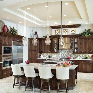 Idee per una grande cucina classica con lavello sottopiano, ante in legno bruno, top in superficie solida, paraspruzzi multicolore, paraspruzzi con piastrelle a mosaico, elettrodomestici in acciaio inossidabile, pavimento in travertino e ante con riquadro incassato