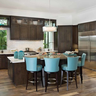 Photo of a mid-sized contemporary l-shaped open plan kitchen in Orlando with a farmhouse sink, shaker cabinets, dark wood cabinets, zinc benchtops, white splashback, porcelain splashback, stainless steel appliances, dark hardwood floors and with island.