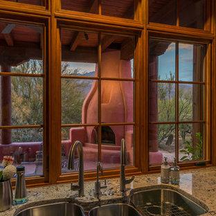 Пример оригинального дизайна интерьера: отдельная кухня с тройной раковиной, фасадами с утопленной филенкой, коричневыми фасадами, столешницей из гранита, техникой из нержавеющей стали, полом из терракотовой плитки и розовым полом без острова