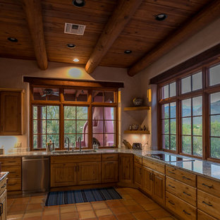 他の地域のサンタフェスタイルのおしゃれな独立型キッチン (トリプルシンク、落し込みパネル扉のキャビネット、茶色いキャビネット、御影石カウンター、シルバーの調理設備の、テラコッタタイルの床、アイランドなし、ピンクの床) の写真