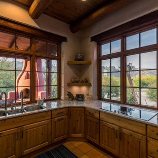 Southwestern enclosed kitchen inspiration - Inspiration for a southwestern terra-cotta floor and pink floor enclosed kitchen remodel in Other with a triple-bowl sink, recessed-panel cabinets, brown cabinets, granite countertops, stainless steel appliances and no island