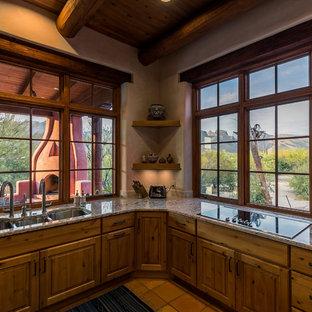 他の地域のサンタフェスタイルのおしゃれな独立型キッチン (トリプルシンク、落し込みパネル扉のキャビネット、茶色いキャビネット、御影石カウンター、シルバーの調理設備、テラコッタタイルの床、アイランドなし、ピンクの床) の写真