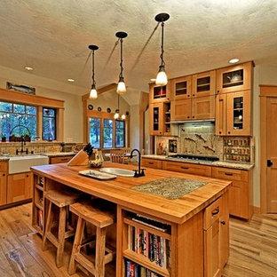 シアトルの中サイズのラスティックスタイルのおしゃれなキッチン (エプロンフロントシンク、シェーカースタイル扉のキャビネット、淡色木目調キャビネット、御影石カウンター、ベージュキッチンパネル、モザイクタイルのキッチンパネル、シルバーの調理設備の、濃色無垢フローリング) の写真