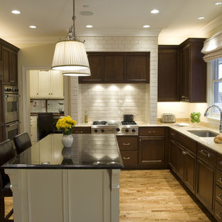 Traditional kitchen remodeling - Example of a classic u-shaped kitchen design in Chicago with subway tile backsplash, an undermount sink, recessed-panel cabinets, dark wood cabinets, granite countertops, white backsplash and paneled appliances