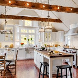 Diseño de cocina comedor en L, tradicional, con fregadero sobremueble, armarios estilo shaker, puertas de armario blancas, salpicadero blanco, salpicadero de azulejos tipo metro, electrodomésticos de acero inoxidable, suelo de madera en tonos medios y una isla