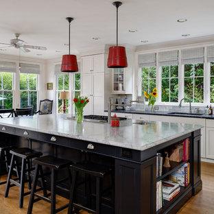 Esempio di una grande cucina tradizionale con lavello sottopiano, ante bianche, paraspruzzi a finestra, pavimento in legno massello medio, ante in stile shaker, top in saponaria, paraspruzzi bianco, elettrodomestici in acciaio inossidabile, pavimento marrone e top nero