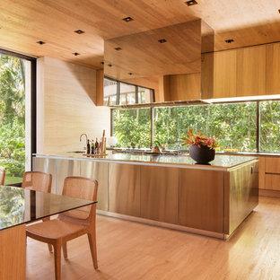 マイアミのトロピカルスタイルのおしゃれなアイランドキッチン (フラットパネル扉のキャビネット、淡色木目調キャビネット、ガラスまたは窓のキッチンパネル、淡色無垢フローリング、ステンレスカウンター) の写真