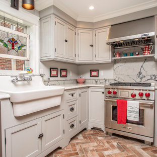 Inredning av ett lantligt vit vitt l-kök, med en rustik diskho, luckor med profilerade fronter, grå skåp, grått stänkskydd, rostfria vitvaror, tegelgolv och brunt golv