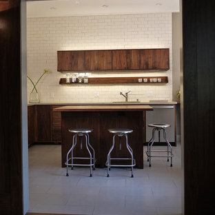 Photo of a mid-sized modern l-shaped separate kitchen in San Francisco with an undermount sink, flat-panel cabinets, dark wood cabinets, white splashback, subway tile splashback, stainless steel appliances, ceramic floors, with island and limestone benchtops.