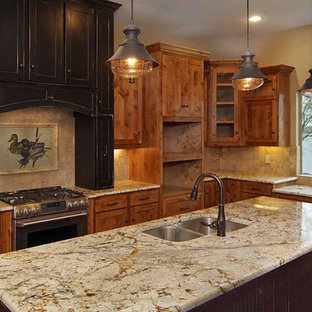 This is an example of a mid-sized arts and crafts l-shaped eat-in kitchen in Dallas with an undermount sink, recessed-panel cabinets, brown cabinets, granite benchtops, beige splashback, limestone splashback, stainless steel appliances, medium hardwood floors, with island and brown floor.