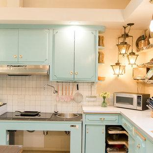 Idee per una cucina chic con lavello sottopiano, ante turchesi, paraspruzzi beige, paraspruzzi con piastrelle in ceramica, elettrodomestici in acciaio inossidabile, pavimento in gres porcellanato, isola, pavimento multicolore e top bianco