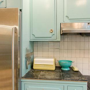 На фото: угловые кухни в стиле современная классика с обеденным столом, врезной раковиной, бирюзовыми фасадами, бежевым фартуком, фартуком из керамической плитки, техникой из нержавеющей стали, полом из керамогранита, островом, разноцветным полом и белой столешницей
