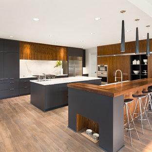 トロントの大きいモダンスタイルのおしゃれなキッチン (アンダーカウンターシンク、フラットパネル扉のキャビネット、中間色木目調キャビネット、白いキッチンパネル、シルバーの調理設備、無垢フローリング、茶色い床、白いキッチンカウンター、石スラブのキッチンパネル) の写真