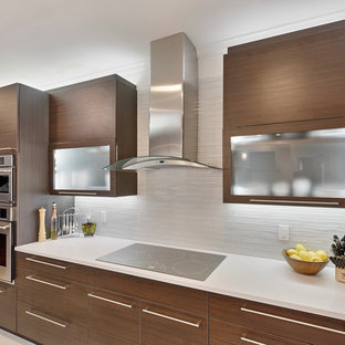 Mid-sized modern l-shaped separate kitchen in Miami with a double-bowl sink, flat-panel cabinets, dark wood cabinets, solid surface benchtops, white splashback, glass tile splashback, stainless steel appliances, porcelain floors and a peninsula.