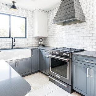 Inspiration för ett avskilt, stort lantligt svart svart l-kök, med en rustik diskho, skåp i shakerstil, blå skåp, bänkskiva i kvarts, vitt stänkskydd, stänkskydd i tunnelbanekakel, svarta vitvaror, marmorgolv, en köksö och grått golv