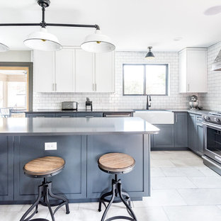 This is an example of a large country l-shaped kitchen in Wilmington with a farmhouse sink, shaker cabinets, blue cabinets, white splashback, subway tile splashback, with island, quartz benchtops, black appliances, marble floors, grey floor and black benchtop.