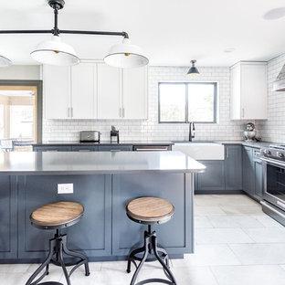 Bild på ett avskilt, stort lantligt svart svart l-kök, med en rustik diskho, skåp i shakerstil, blå skåp, vitt stänkskydd, stänkskydd i tunnelbanekakel, en köksö, bänkskiva i kvarts, svarta vitvaror, marmorgolv och grått golv