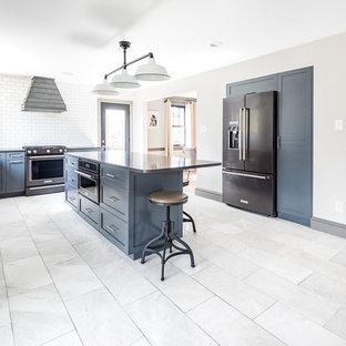 リッチモンドの大きいカントリー風おしゃれなキッチン (エプロンフロントシンク、シェーカースタイル扉のキャビネット、青いキャビネット、クオーツストーンカウンター、白いキッチンパネル、サブウェイタイルのキッチンパネル、黒い調理設備、大理石の床、グレーの床、黒いキッチンカウンター) の写真