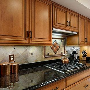 ワシントンD.C.のトランジショナルスタイルのおしゃれなダイニングキッチン (シングルシンク、レイズドパネル扉のキャビネット、中間色木目調キャビネット、御影石カウンター、マルチカラーのキッチンパネル、スレートのキッチンパネル、シルバーの調理設備、セラミックタイルの床、ベージュの床、茶色いキッチンカウンター) の写真