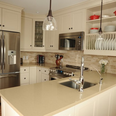 Small country u-shaped medium tone wood floor kitchen photo in Toronto with an undermount sink, shaker cabinets, white cabinets, solid surface countertops, beige backsplash, stone tile backsplash, stainless steel appliances and a peninsula