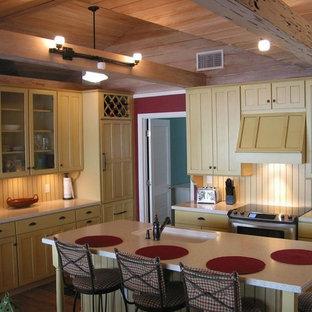 Стильный дизайн: п-образная кухня среднего размера в стиле современная классика с врезной раковиной, фасадами в стиле шейкер, островом, коричневым полом, обеденным столом, желтыми фасадами, столешницей терраццо, желтым фартуком, фартуком из дерева, техникой под мебельный фасад, паркетным полом среднего тона и разноцветной столешницей - последний тренд