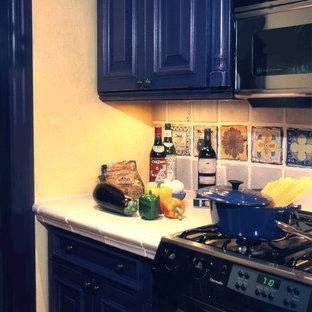Idée de décoration pour une cuisine méditerranéenne avec un placard avec porte à panneau surélevé, des portes de placard bleues, un plan de travail en carrelage et une crédence multicolore.