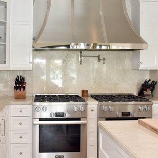 マイアミのヴィクトリアン調のおしゃれなキッチン (アンダーカウンターシンク、落し込みパネル扉のキャビネット、白いキャビネット、御影石カウンター、ベージュキッチンパネル、石スラブのキッチンパネル、シルバーの調理設備の) の写真