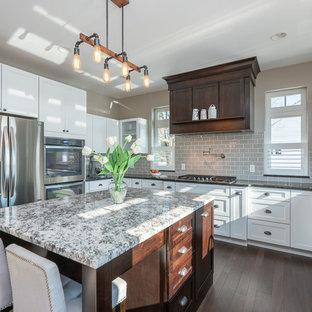 Idéer för att renovera ett stort vintage flerfärgad flerfärgat u-kök, med vita skåp, grått stänkskydd, rostfria vitvaror, mörkt trägolv, en köksö, brunt golv, en dubbel diskho, släta luckor, granitbänkskiva och stänkskydd i keramik