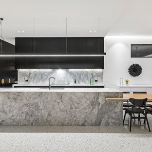 This is an example of a large contemporary l-shaped eat-in kitchen in Melbourne with an undermount sink, flat-panel cabinets, black cabinets, grey splashback, black appliances, with island, grey benchtop, marble benchtops, marble splashback, concrete floors and white floor.