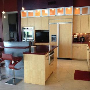 フェニックスの大きいエクレクティックスタイルのおしゃれなキッチン (フラットパネル扉のキャビネット、淡色木目調キャビネット、人工大理石カウンター、メタリックのキッチンパネル、パネルと同色の調理設備、アンダーカウンターシンク、ベージュの床、ボーダータイルのキッチンパネル、セラミックタイルの床) の写真