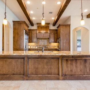 ヒューストンの広い地中海スタイルのおしゃれなキッチン (ドロップインシンク、落し込みパネル扉のキャビネット、茶色いキャビネット、御影石カウンター、ベージュキッチンパネル、石タイルのキッチンパネル、シルバーの調理設備、トラバーチンの床、ベージュの床、ベージュのキッチンカウンター) の写真