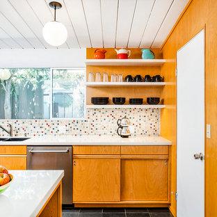 Zweizeilige, Mittelgroße, Offene Mid-Century Küche mit Unterbauwaschbecken, flächenbündigen Schrankfronten, bunter Rückwand, Küchengeräten aus Edelstahl, Halbinsel, schwarzem Boden, weißer Arbeitsplatte, hellbraunen Holzschränken, Mineralwerkstoff-Arbeitsplatte, Rückwand aus Mosaikfliesen und Schieferboden in Los Angeles