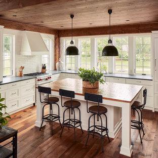 Foto på ett lantligt svart l-kök, med en rustik diskho, skåp i shakerstil, vita skåp, integrerade vitvaror, mörkt trägolv, en köksö och brunt golv