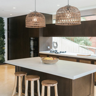 Photo of a tropical kitchen in Sydney with flat-panel cabinets, dark wood cabinets, window splashback, with island, beige floor and white benchtop.