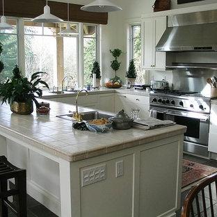 Asiatisk inredning av ett litet kök, med en dubbel diskho, skåp i shakerstil, vita skåp, kaklad bänkskiva, stänkskydd med metallisk yta, stänkskydd i metallkakel, rostfria vitvaror, klinkergolv i keramik och en halv köksö