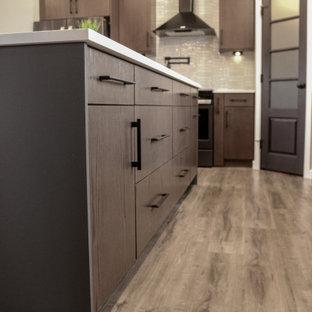 他の地域の広いカントリー風おしゃれなキッチン (エプロンフロントシンク、フラットパネル扉のキャビネット、濃色木目調キャビネット、珪岩カウンター、白いキッチンパネル、セラミックタイルのキッチンパネル、シルバーの調理設備、クッションフロア、茶色い床、白いキッチンカウンター) の写真