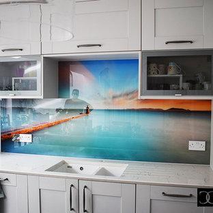 Diseño de cocina comedor moderna, grande, sin isla, con puertas de armario blancas, salpicadero multicolor, salpicadero de vidrio templado y encimeras turquesas