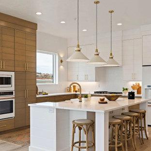 Idéer för ett klassiskt vit l-kök, med en rustik diskho, vita skåp, vitt stänkskydd, vita vitvaror, ljust trägolv och en köksö