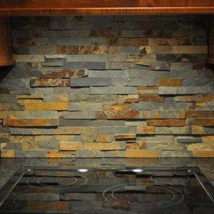 クリーブランドの中サイズのサンタフェスタイルのおしゃれなキッチン (濃色木目調キャビネット、マルチカラーのキッチンパネル、石タイルのキッチンパネル、黒い調理設備) の写真