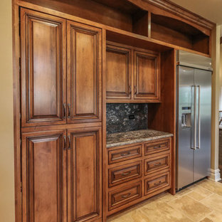 Design ideas for a large country u-shaped eat-in kitchen in Chicago with a farmhouse sink, distressed cabinets, granite benchtops, black splashback, stone slab splashback, stainless steel appliances, travertine floors, with island and beige floor.