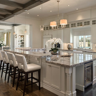 Traditional eat-in kitchen designs - Eat-in kitchen - traditional l-shaped dark wood floor eat-in kitchen idea in Orlando with a farmhouse sink, recessed-panel cabinets, white cabinets, granite countertops, gray backsplash, glass sheet backsplash, stainless steel appliances and an island