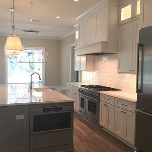 ジャクソンビルのトラディショナルスタイルのおしゃれなキッチン (エプロンフロントシンク、フラットパネル扉のキャビネット、白いキャビネット、珪岩カウンター、白いキッチンパネル、磁器タイルのキッチンパネル、シルバーの調理設備の、クッションフロア、マルチカラーの床、白いキッチンカウンター) の写真