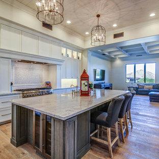 フェニックスの大きいサンタフェスタイルのおしゃれなキッチン (エプロンフロントシンク、シェーカースタイル扉のキャビネット、白いキャビネット、御影石カウンター、白いキッチンパネル、サブウェイタイルのキッチンパネル、シルバーの調理設備の、無垢フローリング) の写真
