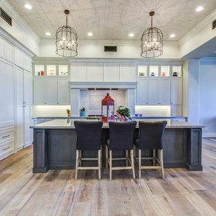 Large southwestern open concept kitchen remodeling - Example of a large southwest l-shaped medium tone wood floor open concept kitchen design in Phoenix with a farmhouse sink, shaker cabinets, white cabinets, granite countertops, white backsplash, subway tile backsplash, stainless steel appliances and an island